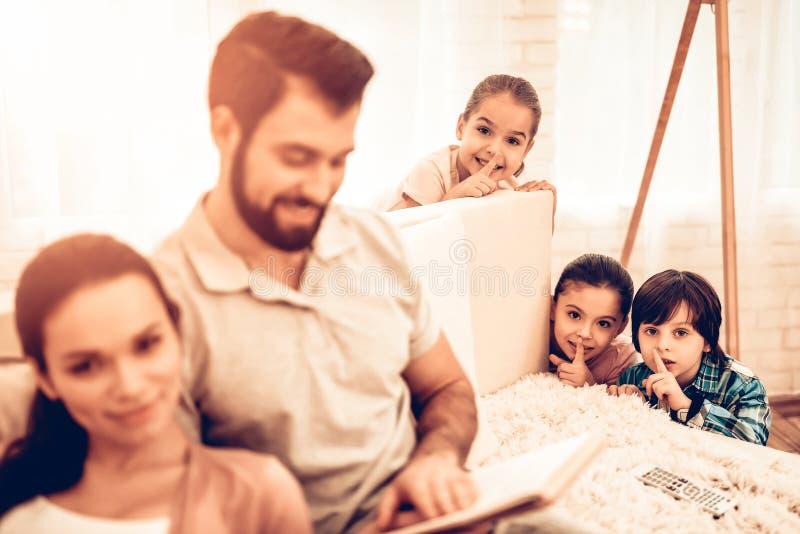 愉快的逗人喜爱的父母看书,当孩子使用时 库存照片