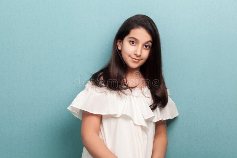 愉快的镇静美丽的深色的少女在白色礼服身分和看照相机画象有黑长的直发的 库存图片