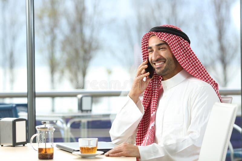 愉快的阿拉伯人谈话在电话在咖啡馆 免版税库存图片