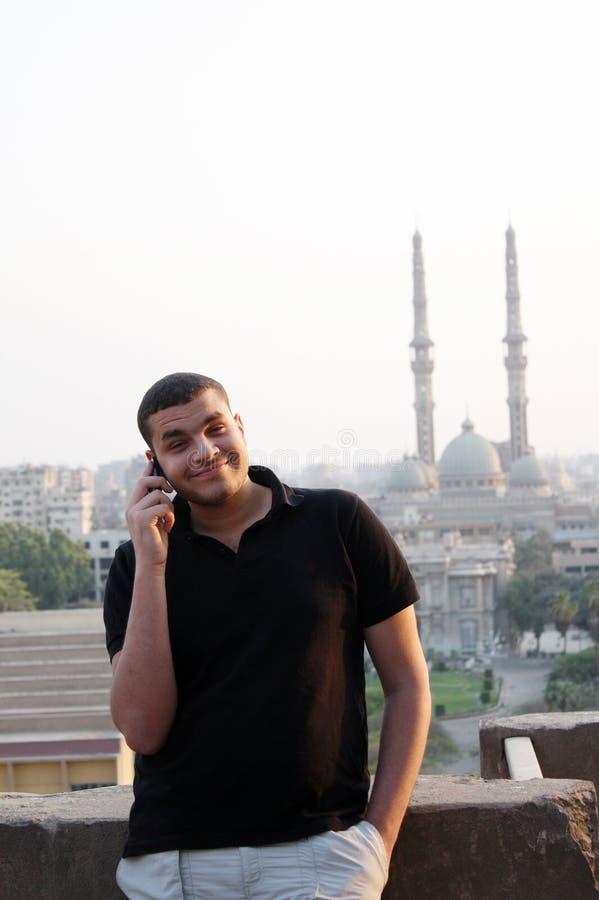 愉快的阿拉伯埃及年轻商人谈话与电话 库存图片