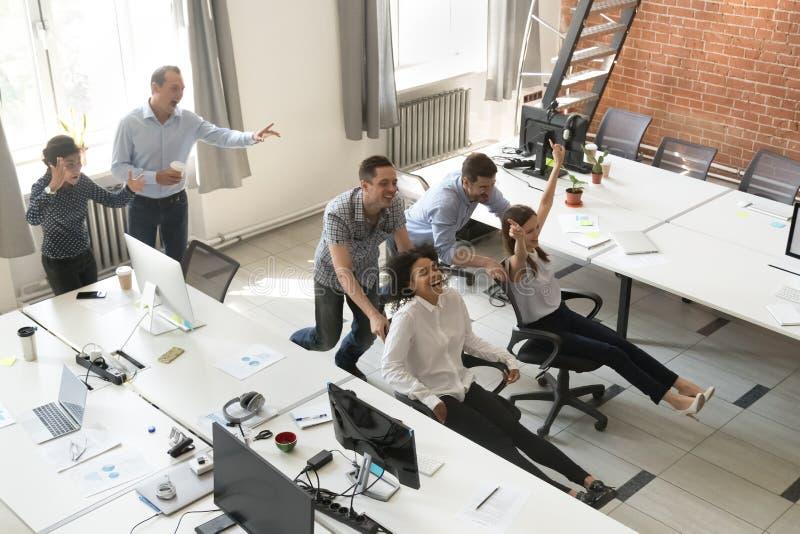 愉快的雇员享受乘坐在offi的椅子的滑稽的竞争 免版税库存图片