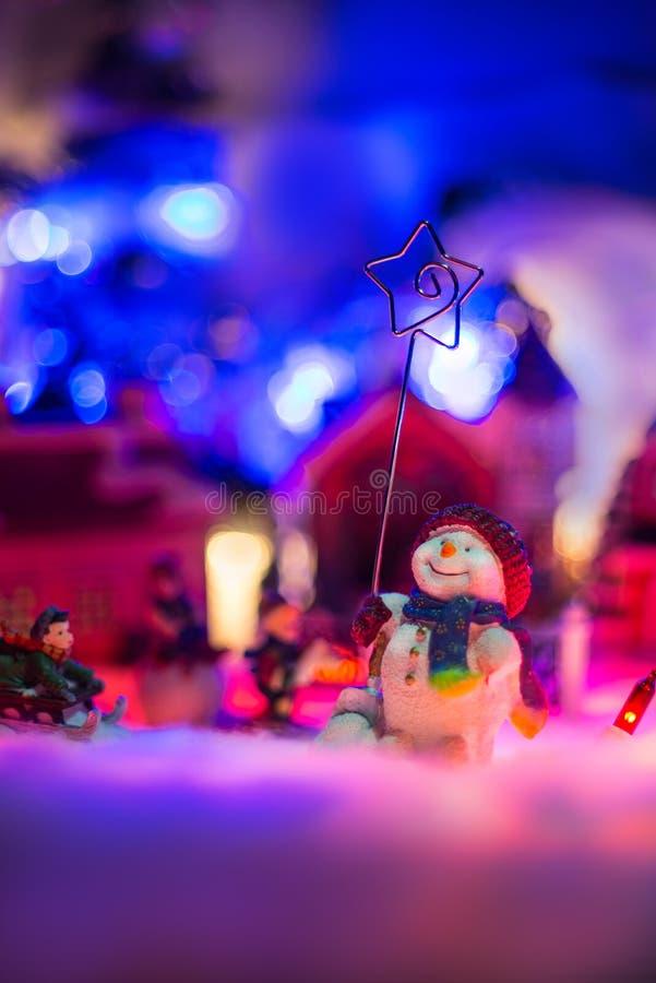 愉快的雪人拿着伯利恒立场星在五颜六色的多雪的村庄前面的在背景中 圣诞节欢乐缩样sce 免版税库存照片