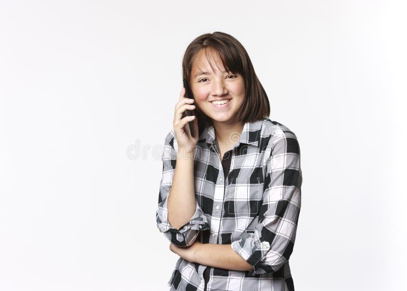 愉快的青少年的女孩谈话在手机 免版税库存照片