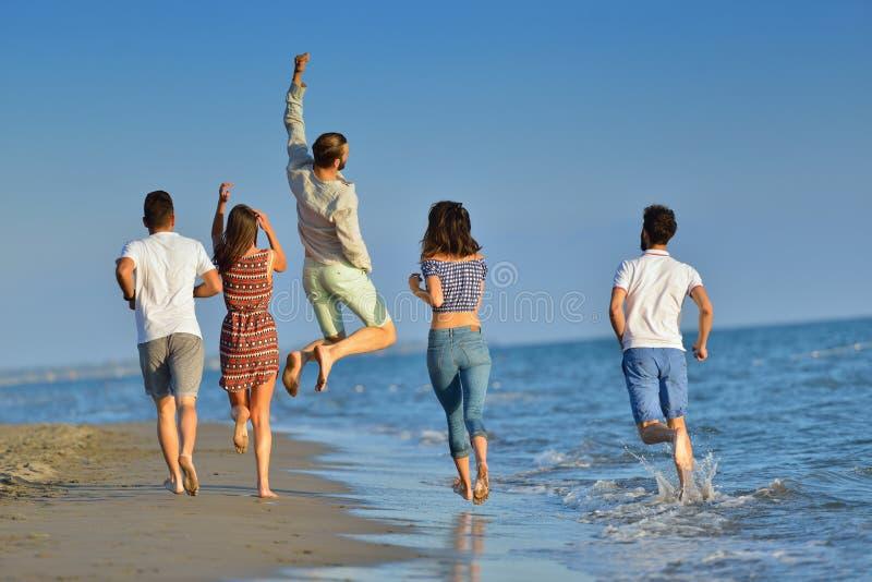 愉快的青年人小组有乐趣白色赛跑和跳在beacz在日落时间 免版税库存图片