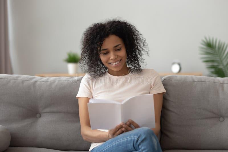 愉快的非洲妇女放松的看书坐沙发 免版税图库摄影