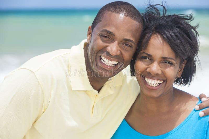 愉快的非洲裔美国人的人妇女夫妇海滩 免版税库存图片