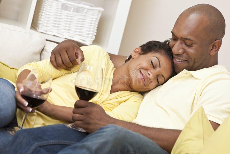 愉快的非洲裔美国人的夫妇饮用的酒 免版税库存图片