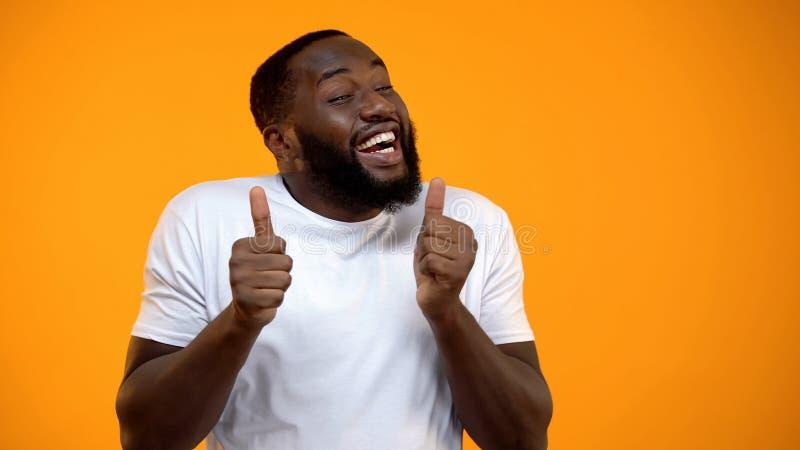愉快的非裔美国人的人欣喜和陈列翘拇指,最佳的生活片刻 免版税库存照片