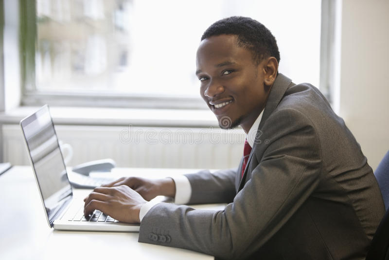 愉快的非裔美国人的商人画象使用膝上型计算机的在办公桌 免版税库存图片