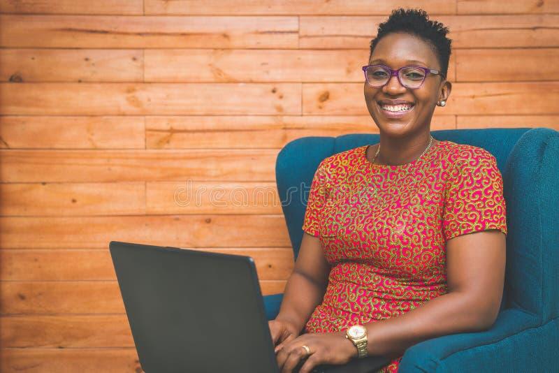 愉快的非裔美国人的夫人在家与膝上型计算机一起使用 免版税库存照片