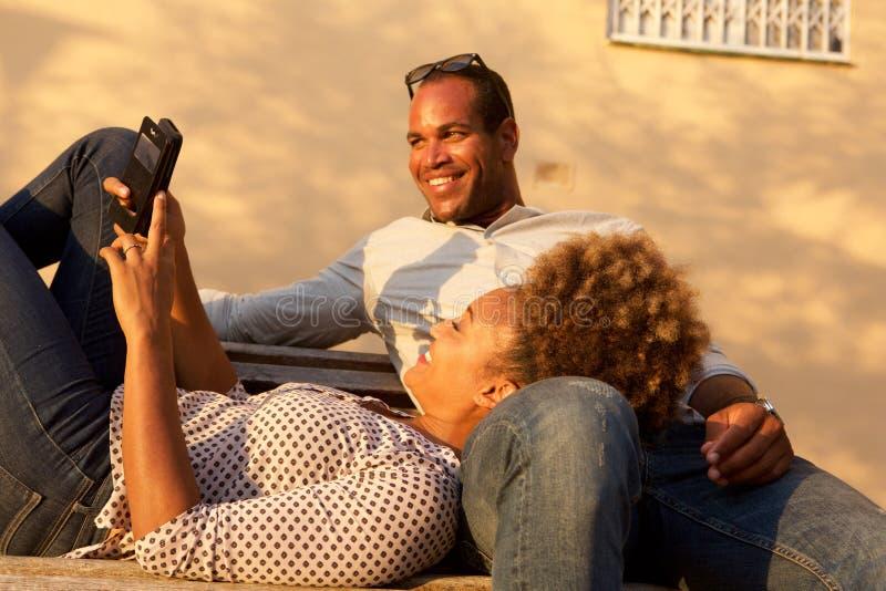 愉快的非裔美国人的夫妇一起在公园长椅 库存照片