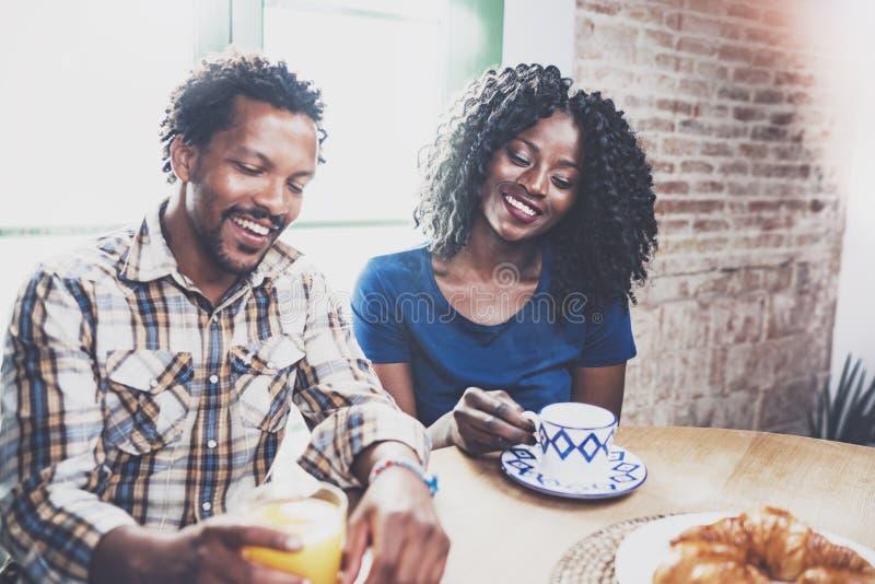 愉快的非裔美国人的夫妇吃早餐一起早晨在木桌上 微笑的黑人和他的 免版税库存照片