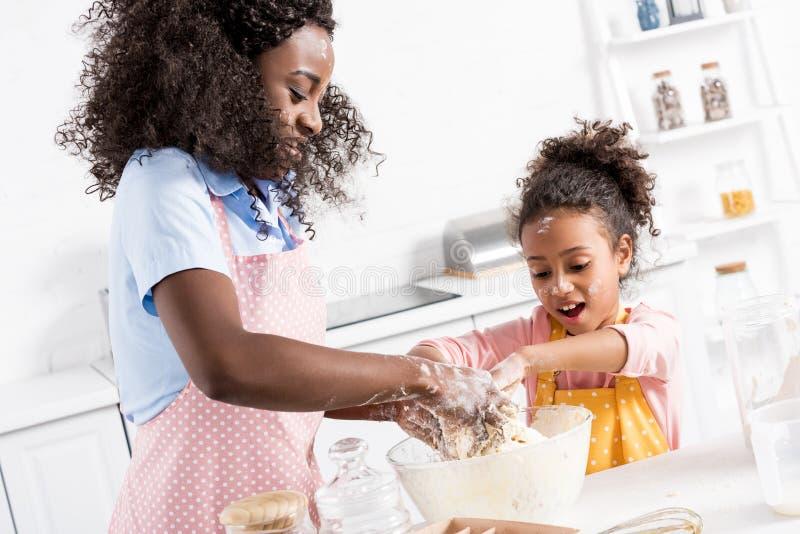 愉快的非裔美国人的母亲和女儿揉的面团 库存图片