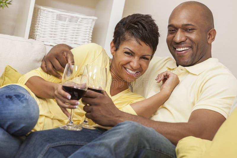愉快的非裔美国人的男人&妇女夫妇饮用的酒 库存照片