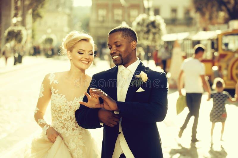 愉快的非裔美国人的走在街道上的新郎和逗人喜爱的新娘 免版税库存照片