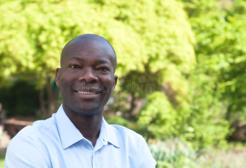 愉快的非洲人在看照相机的公园 免版税图库摄影