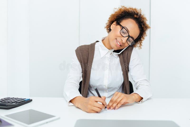 愉快的非洲女会计谈话在手机和写 库存照片