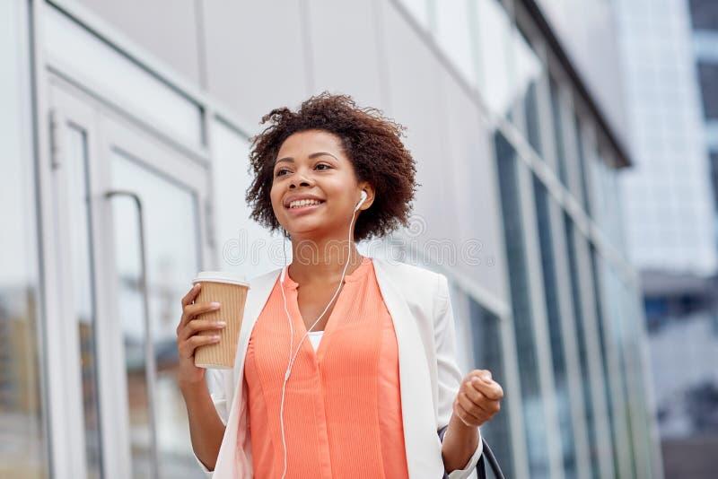 愉快的非洲女实业家用咖啡在城市 免版税图库摄影