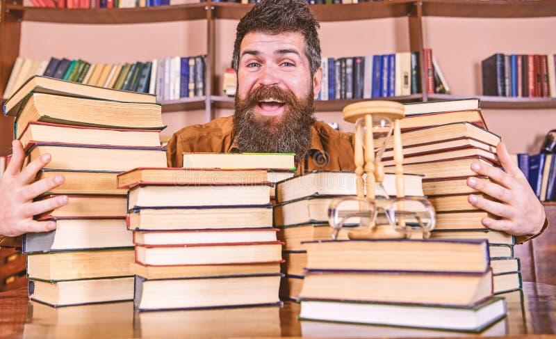 愉快的面孔的人在堆书之间,当学习在图书馆里,在背景时的书架 图书管理员概念 库存图片