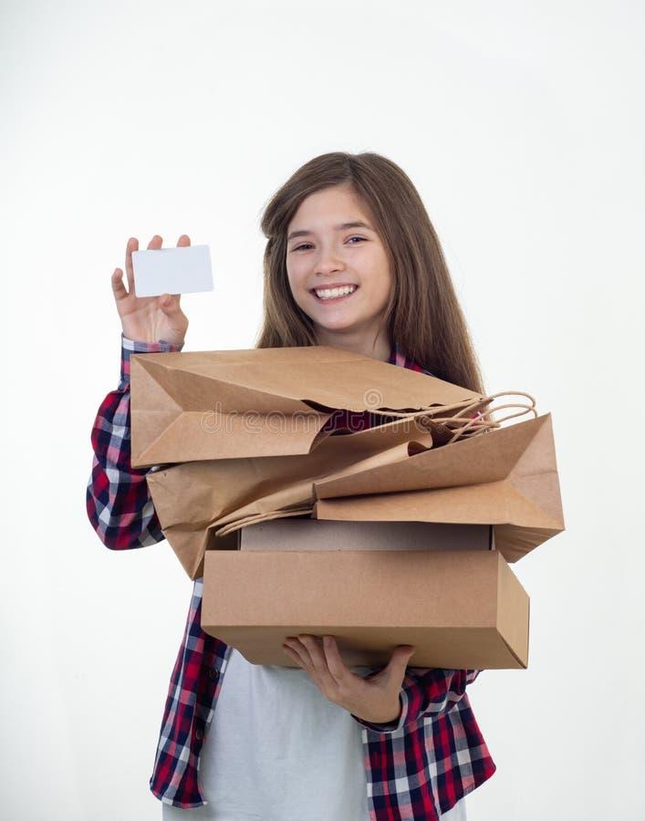 愉快的顾客藏品折扣白色卡片和购物带来和纸盒箱子在她的手上 看板卡赊帐女孩年轻人 库存照片