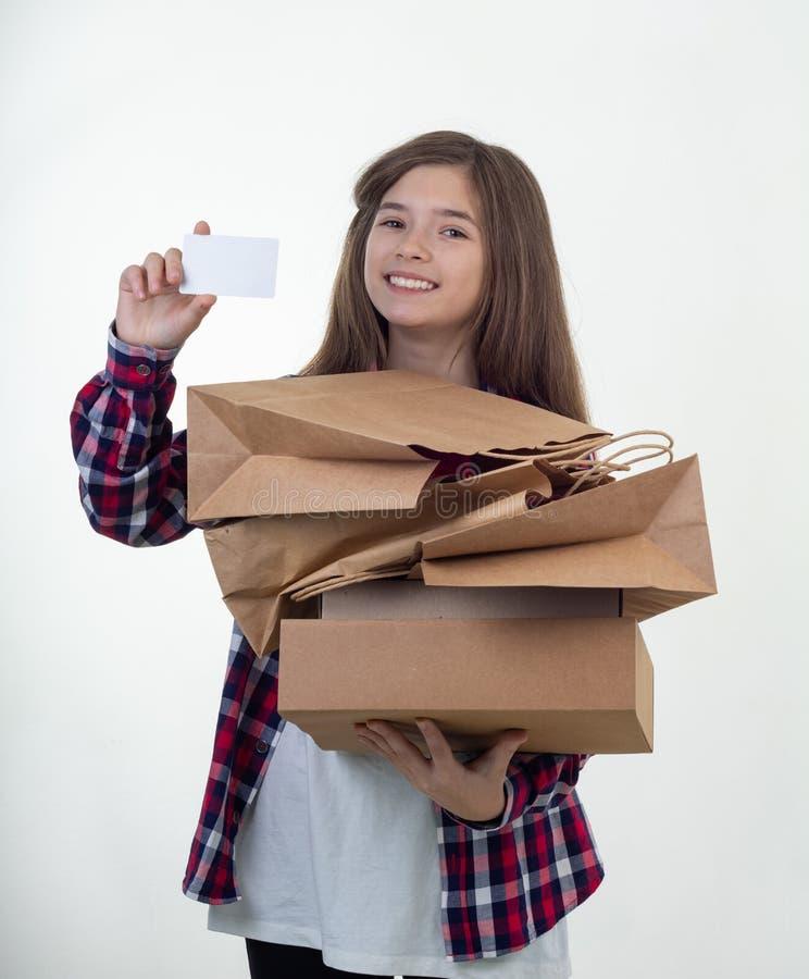 愉快的顾客藏品折扣白色卡片和购物带来和纸盒箱子在她的手上 看板卡赊帐女孩年轻人 免版税库存照片
