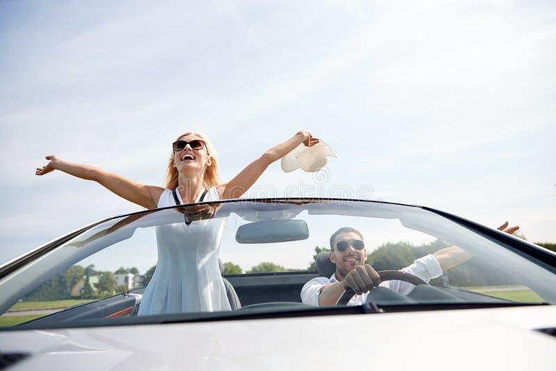 愉快的驾驶在敞蓬车汽车的男人和妇女 库存图片