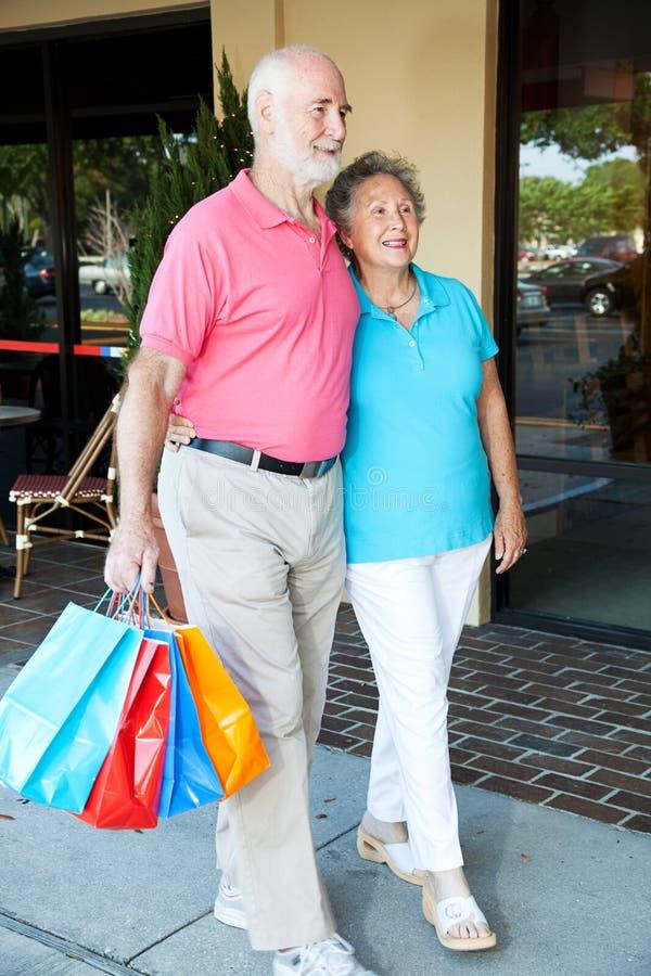愉快的高级夫妇去购物 免版税库存照片
