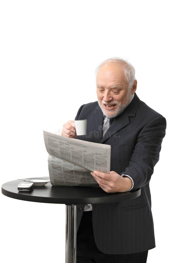 愉快的高级生意人读取报纸 免版税图库摄影