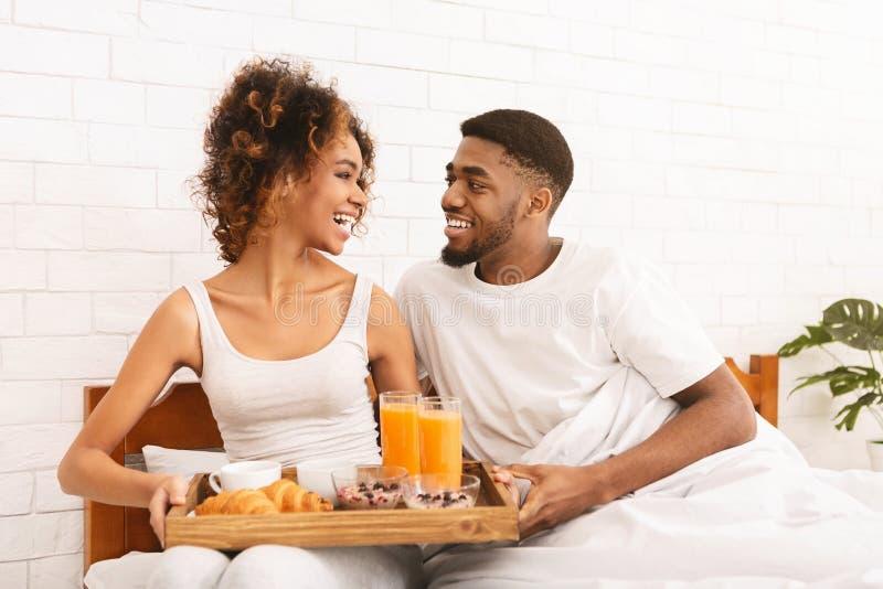 愉快的黑夫妇在床上的享用早餐 图库摄影