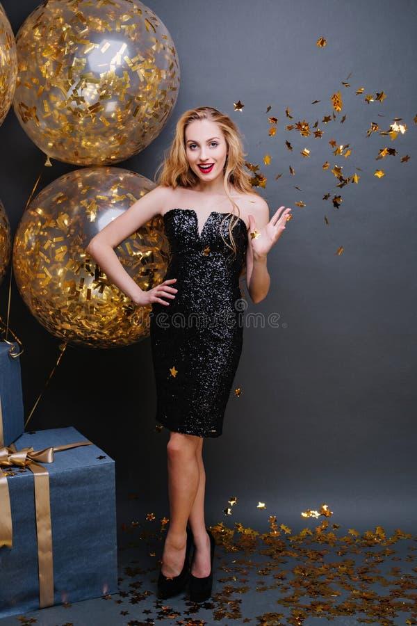 愉快的黑豪华礼服的党时间迷人的年轻女人,在脚跟,有在黑背景的长的卷曲金发的 库存照片