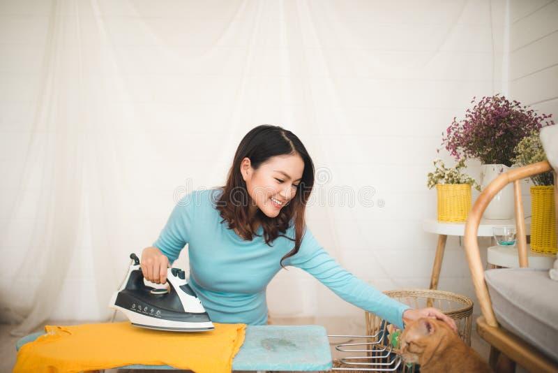 愉快的年轻亚裔妇女电烙的衣裳在家坐地板 免版税图库摄影