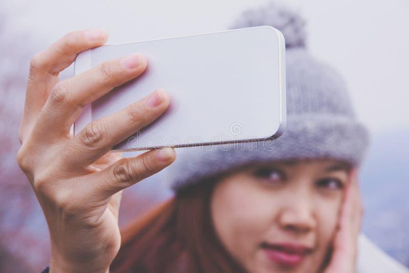 愉快的年轻亚裔妇女看她的手机 免版税库存照片