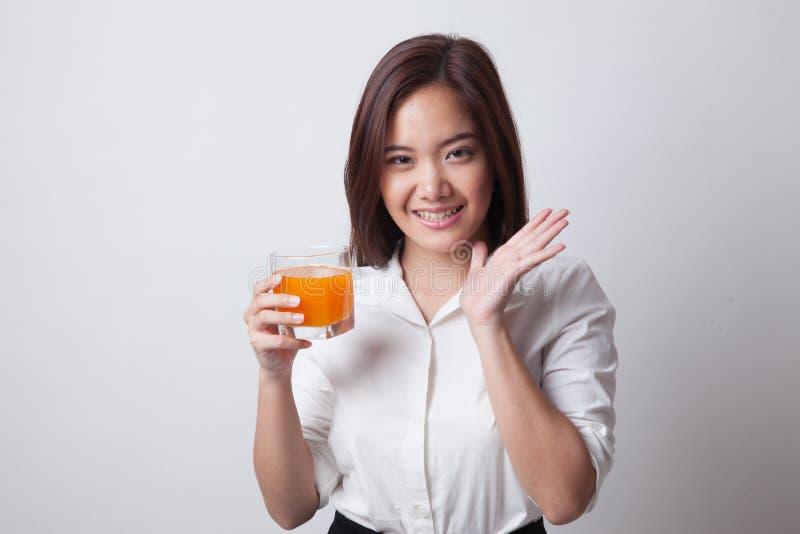 愉快的年轻亚洲妇女饮料橙汁 图库摄影
