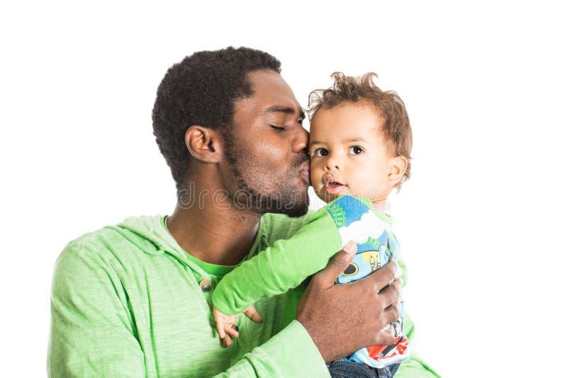 愉快的黑人父亲和拥抱在被隔绝的白色用途它孩子的男婴,做父母 库存照片