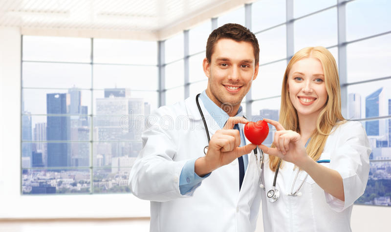 愉快的年轻人医治有红色心脏的心脏科医师 免版税库存照片