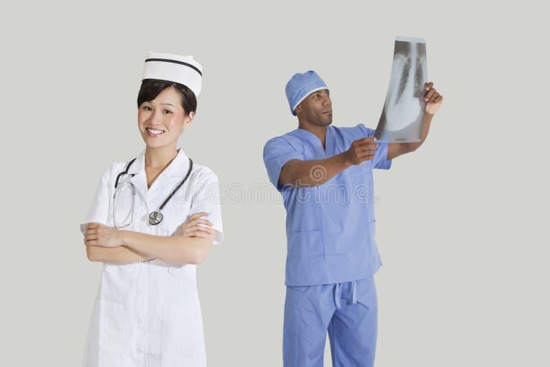 愉快的年轻人画象护理与男性在灰色背景的外科医生审查的X-射线报告 免版税图库摄影