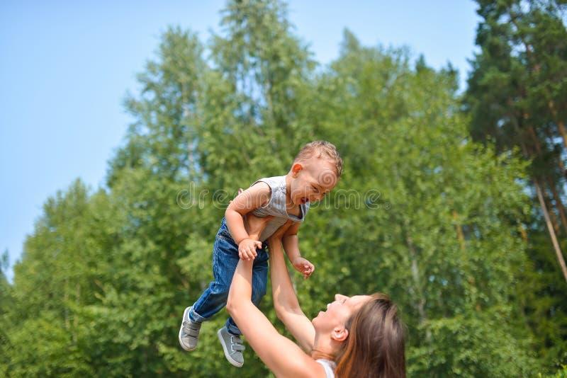 愉快的系列户外 母亲投掷婴孩,笑和使用在自然的夏天 库存照片