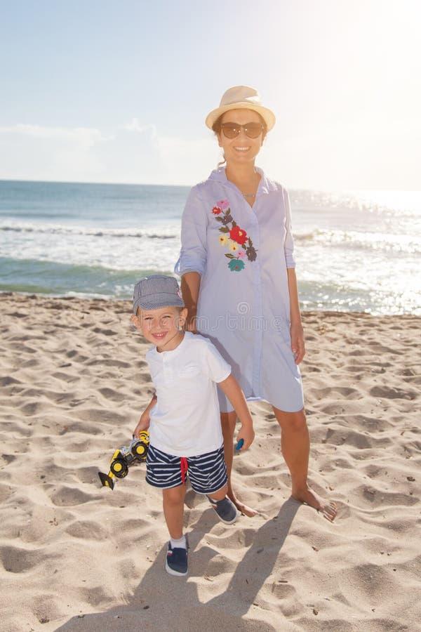 愉快的系列 年轻美丽的获得母亲和她的儿子在海滩的乐趣 免版税库存照片