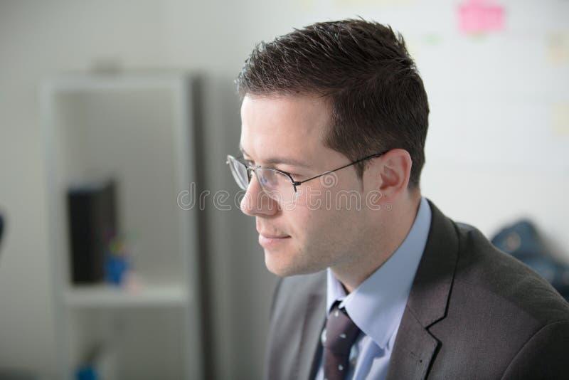 愉快的年轻商人工作在现代办公室 英俊的商人在办公室 真正的经济学家bussinesmen,不是模型 免版税图库摄影