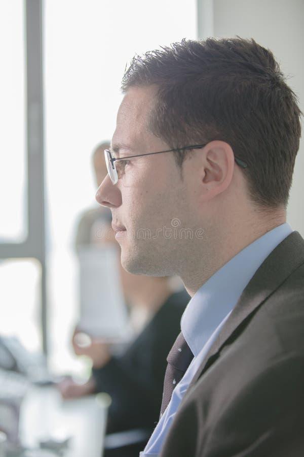 愉快的年轻商人工作在现代办公室 英俊的商人在办公室 真正的经济学家bussinesmen,不是模型 库存照片