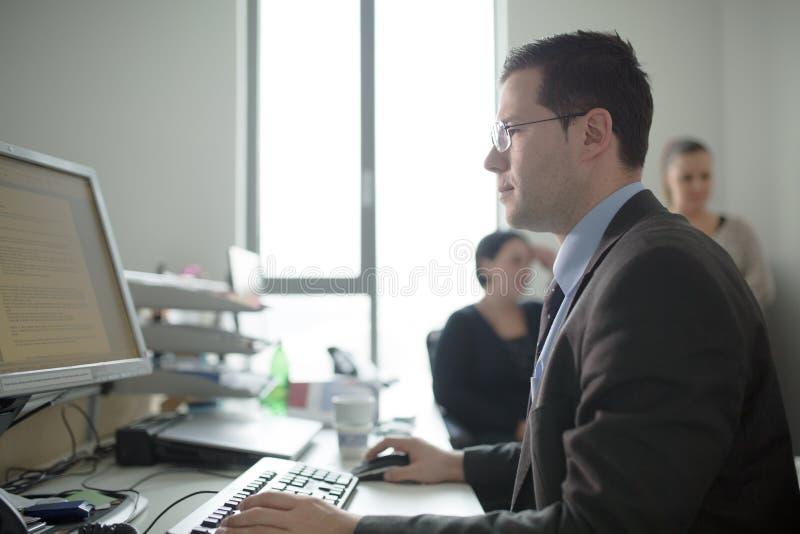 愉快的年轻商人工作在现代办公室 英俊的商人在办公室 真正的经济学家bussinesmen,不是模型 免版税库存照片