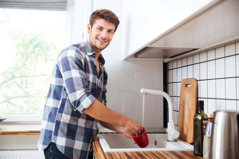 愉快的年轻在厨房的人站立的和洗涤的盘 图库摄影