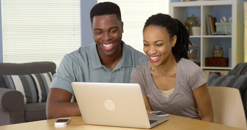 愉快的黑在膝上型计算机的夫妇笑的和观看的录影 图库摄影