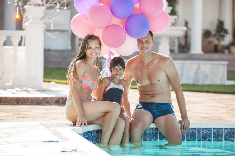 愉快的年轻坐在游泳池边缘的夫妇和女儿 库存图片