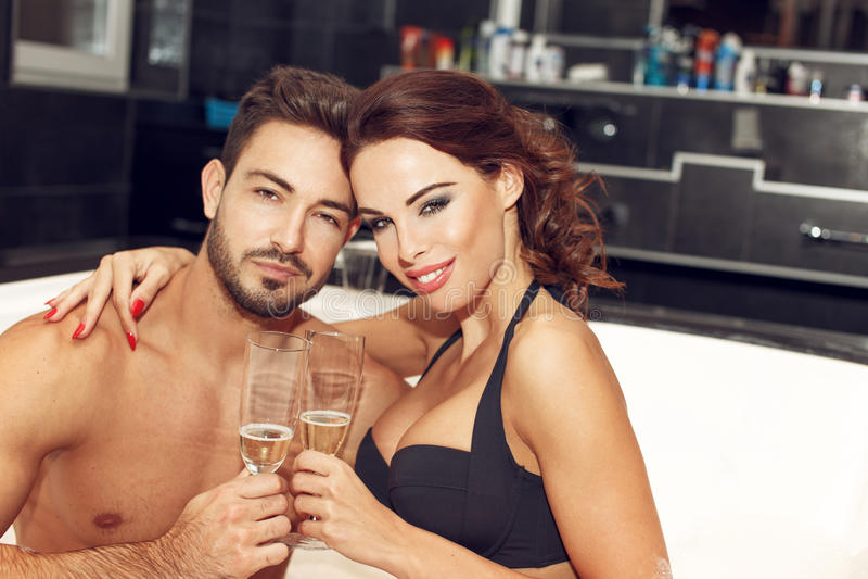 愉快的年轻夫妇喝在极可意浴缸蜜月的香槟 库存图片