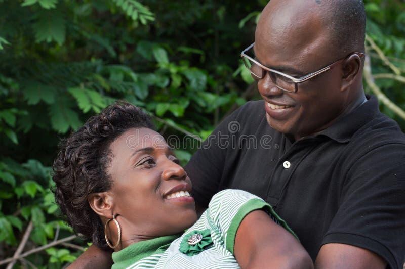 愉快的年轻夫妇在度假在灌木的 库存照片