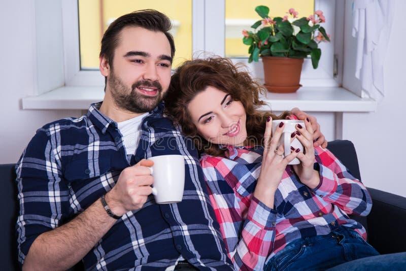 愉快的年轻夫妇坐有茶的沙发或咖啡 图库摄影