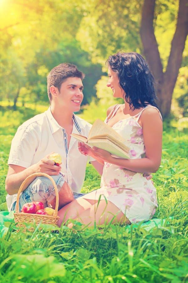 愉快的年轻夫妇坐讲话的草微笑和 库存图片