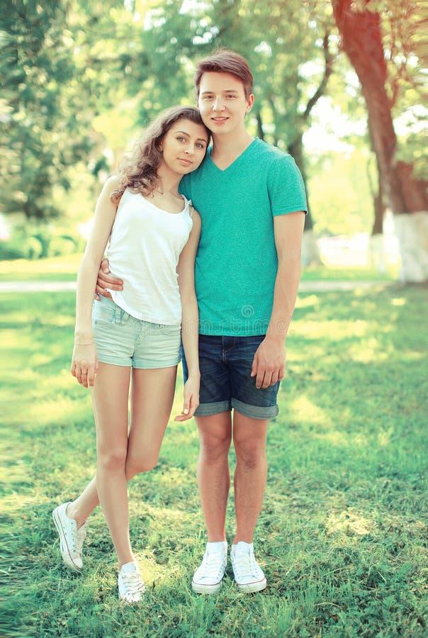 愉快的年轻夫妇少年在草站立 免版税库存图片