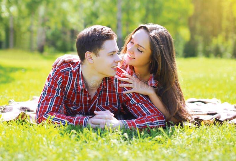 愉快的年轻夫妇获得乐趣在草的公园 免版税库存照片